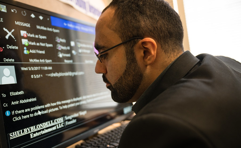 A male worker with a visual impairment uses a large computer screen.
