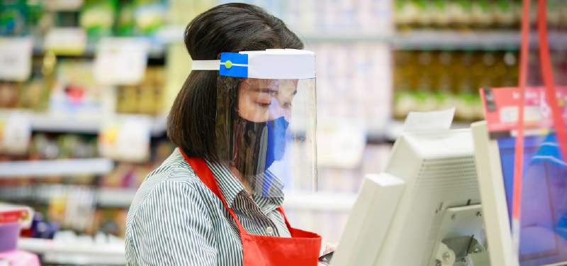 A cashier works at a grocery store wearing protective equipment to prevent viral transmission.