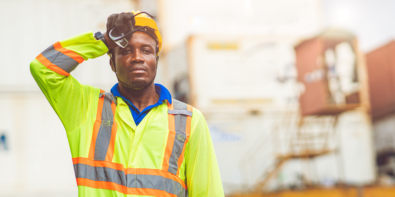 A worker wearing reflective clothing stands outside in the heat, wiping his brow
