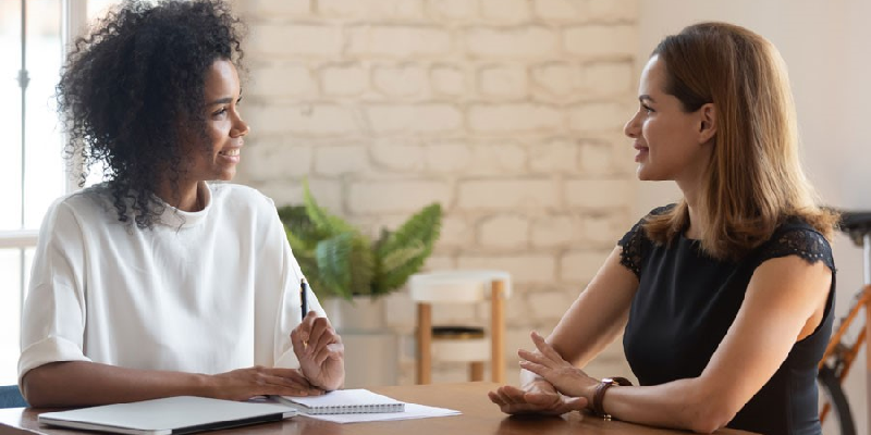 A boss and employee, both women, sit at a table and discuss accommodations.
