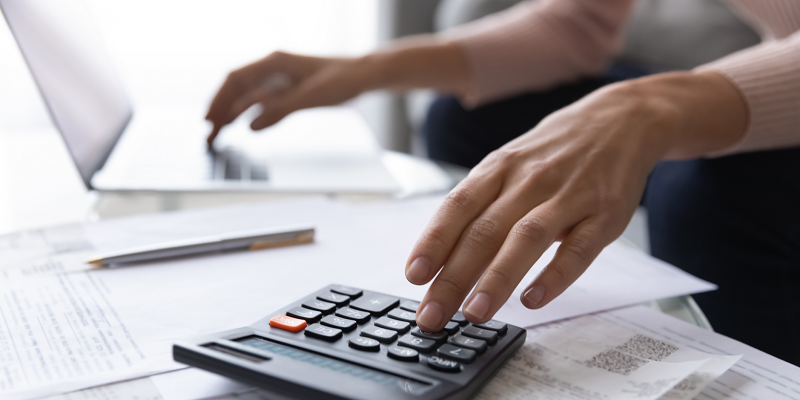 Close up photo of a woman's hands as she reviews retirement planning papers with her computer and calculator nearby