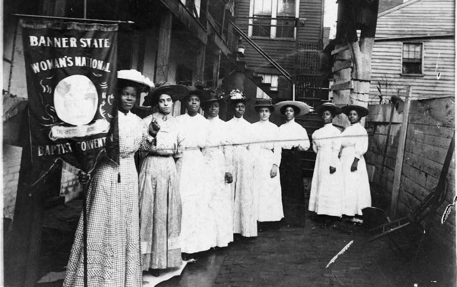 """Nine African-American women posed, standing, full length, with suffragist Nannie Burroughs holding a banner reading, """"Banner State Woman's National Baptist Convention"""